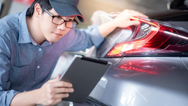 Asian auto mechanic checking the car using tablet. Young Asian auto mechanic holding digital tablet checking tail light in auto service garage. Mechanical stock photo