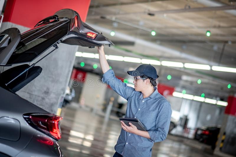Asian auto mechanic checking the car using tablet. Young Asian auto mechanic holding digital tablet checking tailgate in auto service garage. Mechanical stock image
