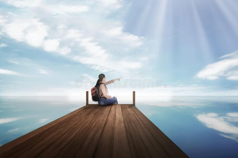 Young asian backpacker woman sitting and pointing blue sky stock photo