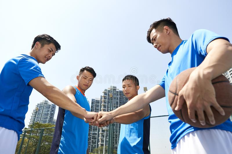 Young asian basketball players putting fists together stock photos