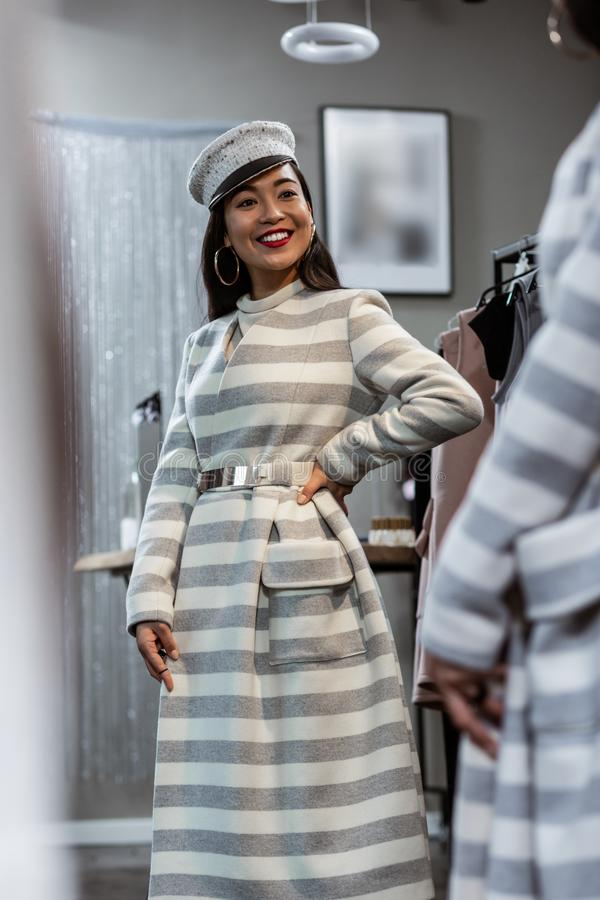 Young asian beaming woman in a striped coat looking happy stock image