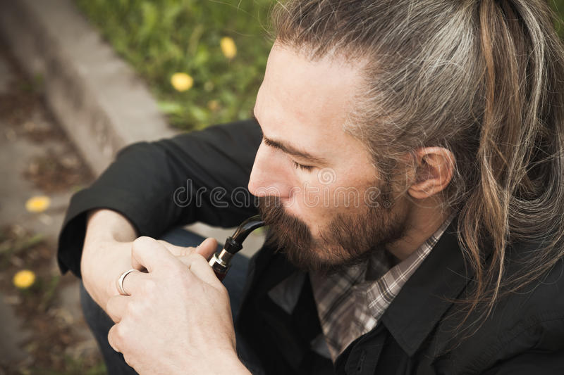 Young asian bearded man smoking pipe. In summer park, close up portrait stock photo