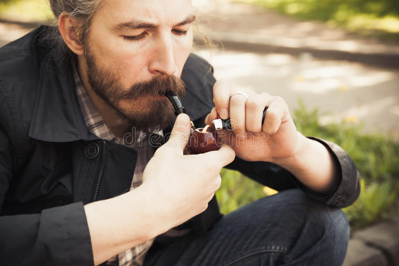 Young asian bearded man smoking a pipe. In summer park, close-up portrait with selective focus stock photography
