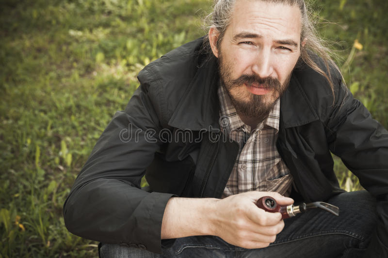 Young asian bearded man smoking pipe. In summer park, closeup portrait stock images