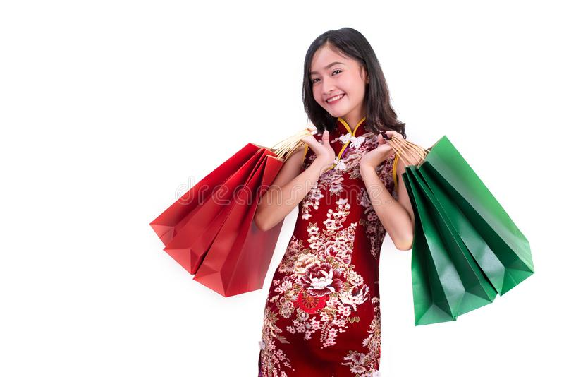 Young Asian beauty woman wearing cheongsam and holding red and green shopping bags gesture in Chinese new year festival event on stock photos