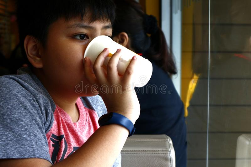 Young Asian boy drink from a paper cup inside a fast food restaurant stock photos