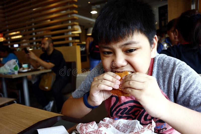Young Asian boy eats a hamburger inside a fast food restaurant. SAN JUAN, METRO MANILA, PHILIPPINES – AUGUST 21, 2019: Young Asian boy eats a hamburger royalty free stock photo