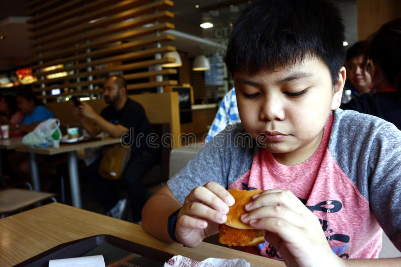 Young Asian boy eats a hamburger inside a fast food restaurant. SAN JUAN, METRO MANILA, PHILIPPINES – AUGUST 21, 2019: Young Asian boy eats a hamburger stock image