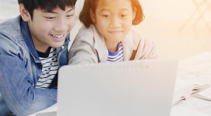 Young asian boy and girl playing with laptop computer at home royalty free stock images