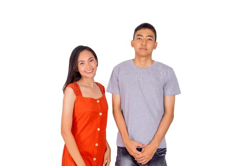 Young Asian boy and girl standing together in front of the camera white background. The Young Asian boy and girl standing together in front of the camera white stock image