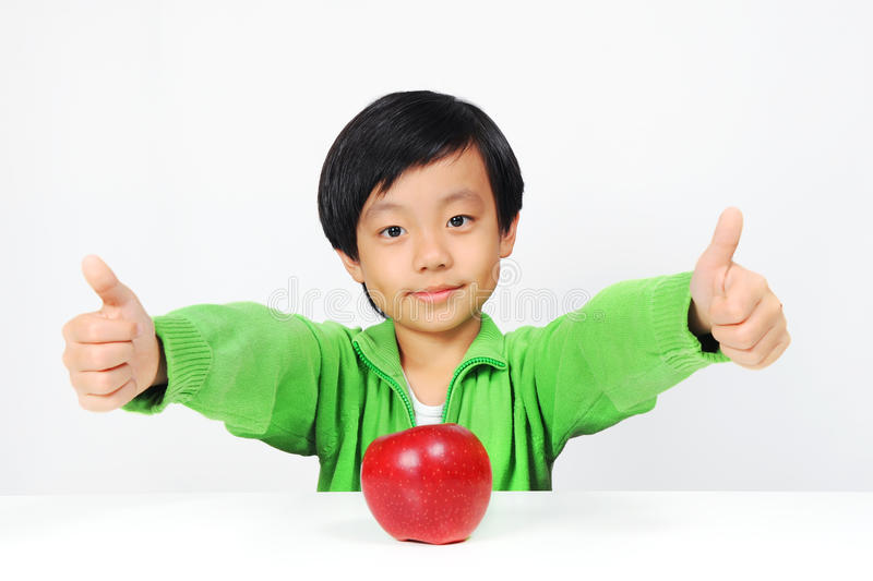 Young Asian boy gives thumbs up for healthy food