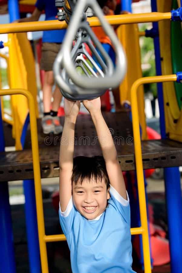 Young asian boy hang the bar. By his hand to exercise at out door playground stock images