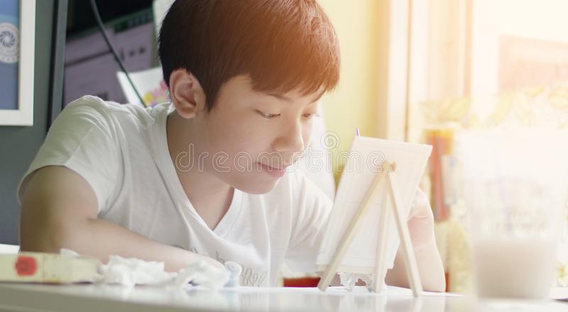 Young asian boy painting water colour at home with smile face royalty free stock photography