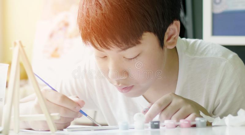 Young asian boy painting water colour at home with smile face stock image