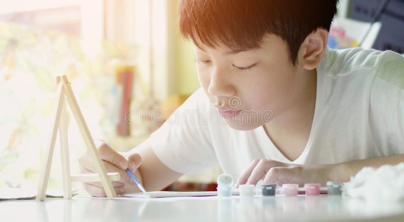 Young asian boy painting water colour at home with smile face stock photography
