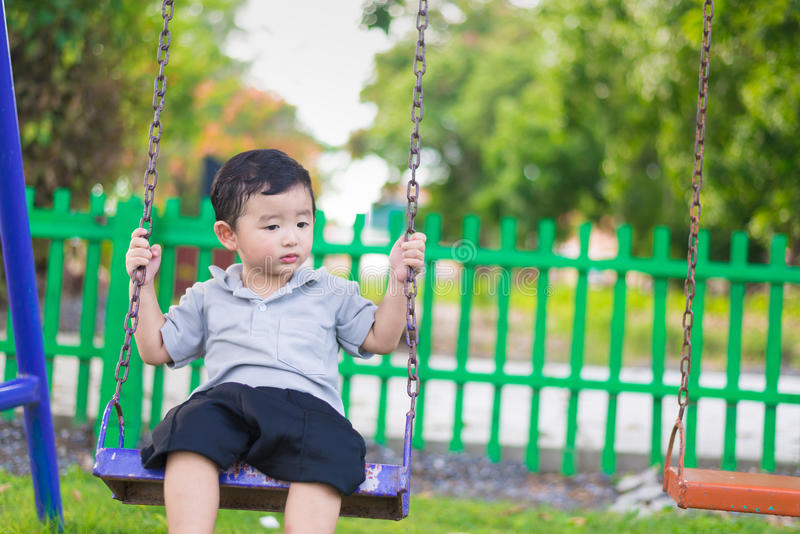 Young Asian boy play a iron swinging at the playground under the. Sunlight in summer, Kids play on school yard. Happy kid in kindergarten or preschool. Children royalty free stock photos
