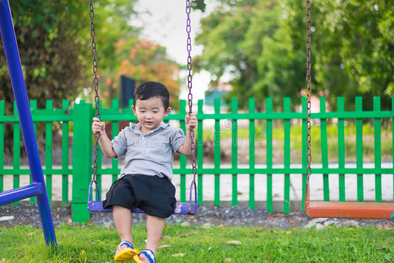 Young Asian boy play a iron swinging at the playground under the. Sunlight in summer, Kids play on school yard. Happy kid in kindergarten or preschool. Children royalty free stock photo