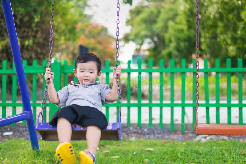 Young Asian boy play a iron swinging at the playground under the. Sunlight in summer, Kids play on school yard. Happy kid in kindergarten or preschool. Children stock images