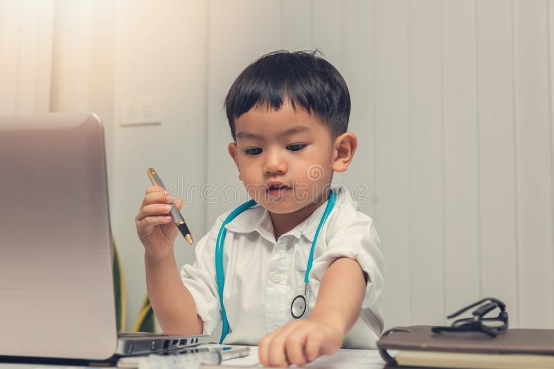 Young asian boy playing doctor and using computer laptop royalty free stock photos