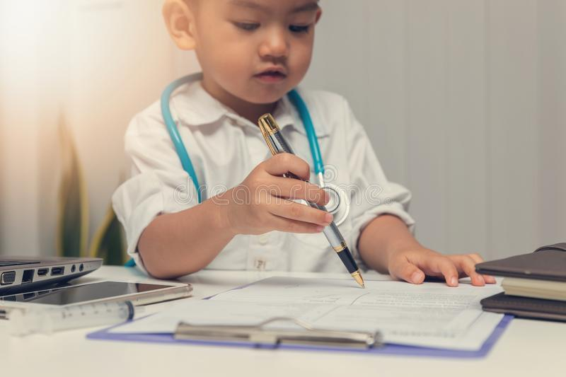 Young asian boy playing doctor and using computer laptop stock photography