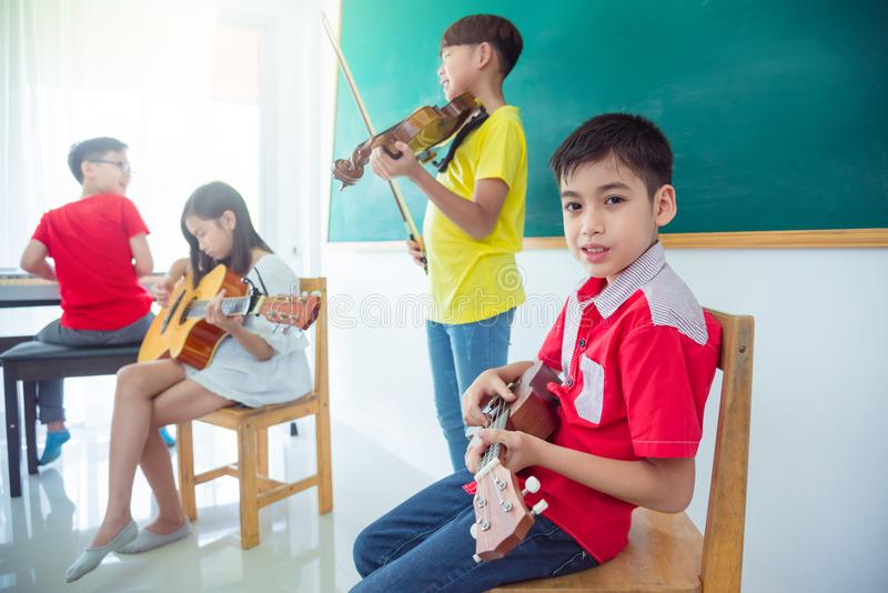 Boy playing ukulele with friends in music classroom. Young asian boy playing ukulele with friends in music classroom stock photography