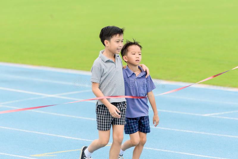 Young Asian boy running on blue track in the stadium. Selective focus at young Asian boy carry each other to finished line royalty free stock photo