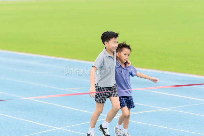 Young Asian boy running on blue track in the stadium. Selective focus at young Asian boy carry each other to finished line royalty free stock photos