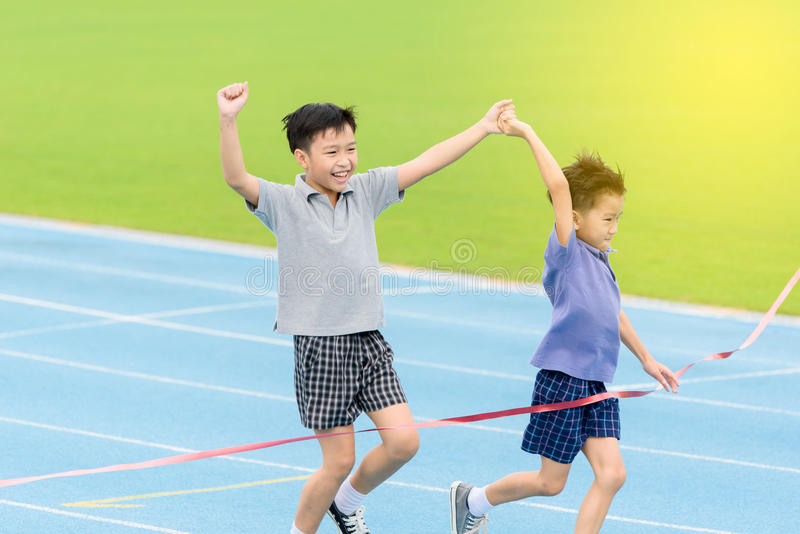 Young Asian boy running on blue track in the stadium. Selective focus at young Asian boy hold hand together running on blue track to the finished line royalty free stock photography