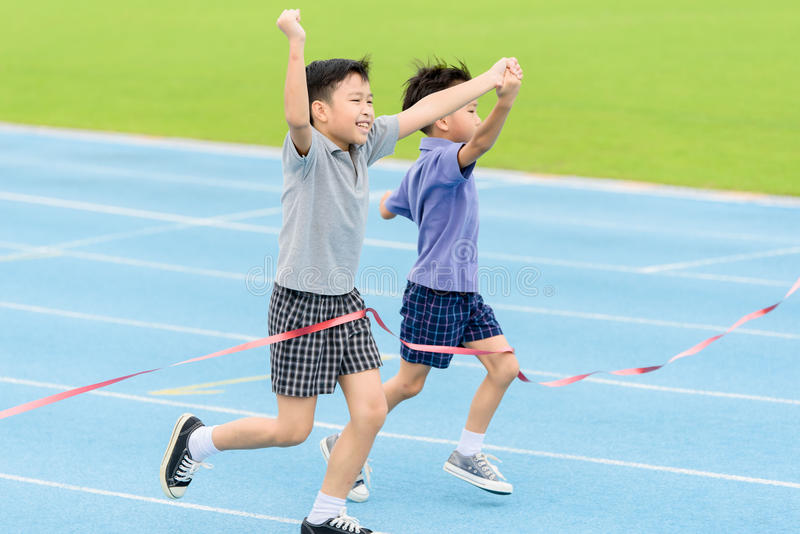 Young Asian boy running on blue track in the stadium. Selective focus at young Asian boy hold hand together running on blue track to the finished line stock photo