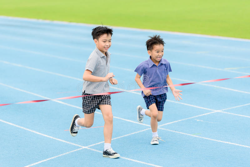 Young Asian boy running on blue track in the stadium royalty free stock photo