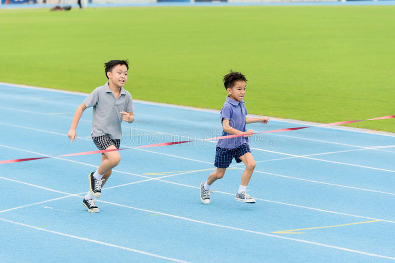 Young Asian boy running on blue track in the stadium. Selective focus at young Asian boy running on blue track to the finished line royalty free stock photography