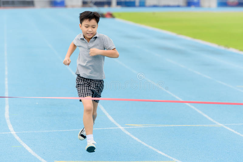 Young Asian boy running on blue track in the stadium. Selective focus at young Asian boy running on blue track to the finished line royalty free stock images