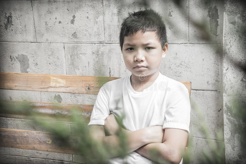 Young Asian boy sitting alone in the park royalty free stock photography