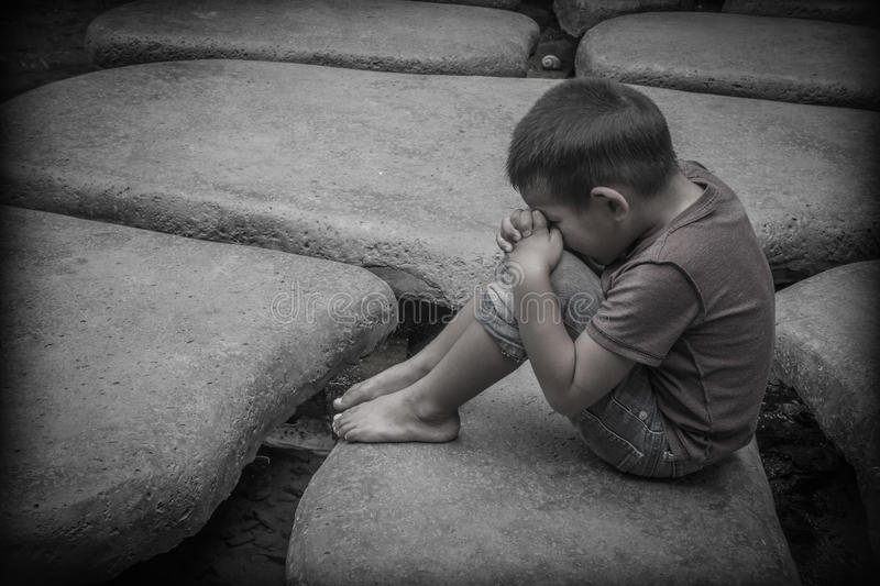A young Asian boy sitting praying on the rocks stock photography