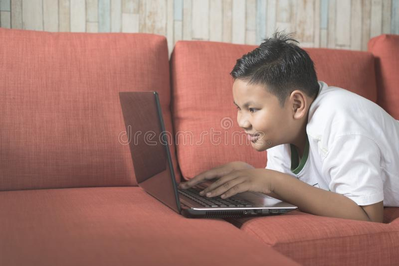 Young asian boy smiling using laptop computer on a sofa at home. stock photos