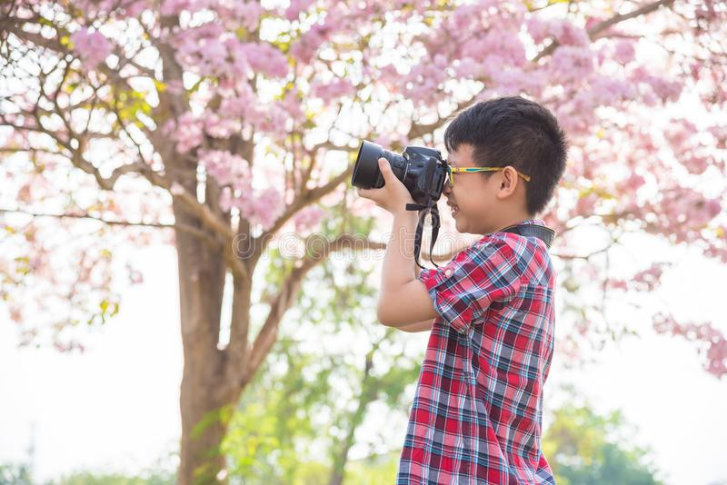 Young boy taking photo by camera in park stock photography