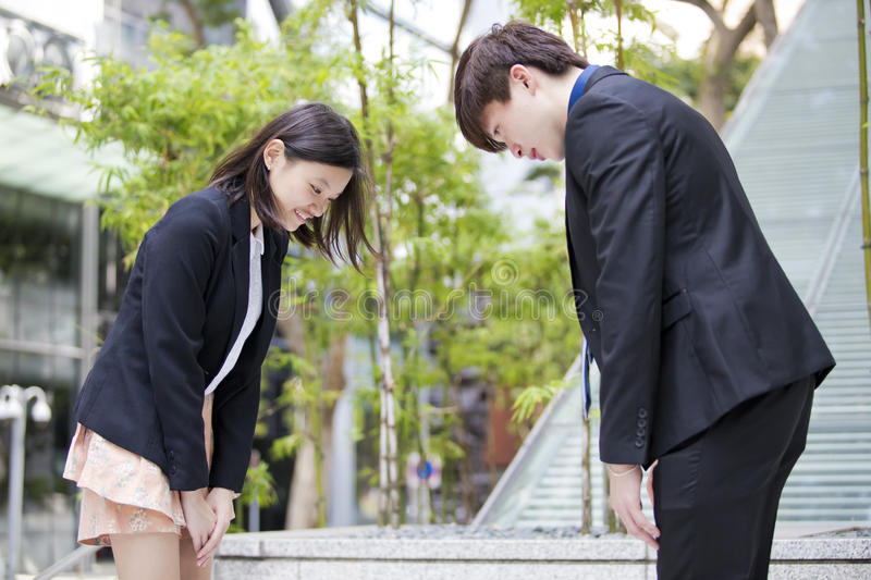 Young Asian business executives bowing to each other. Asian culture royalty free stock photo