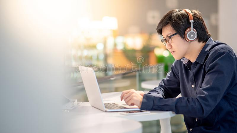 Young Asian business man listening to music while working with l royalty free stock photos