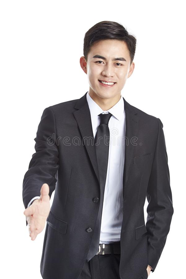 Young asian business man reaching out for a handshake. Studio shot of a young asian businessman reaching out for a handshake, looking at camera smiling, isolated stock images