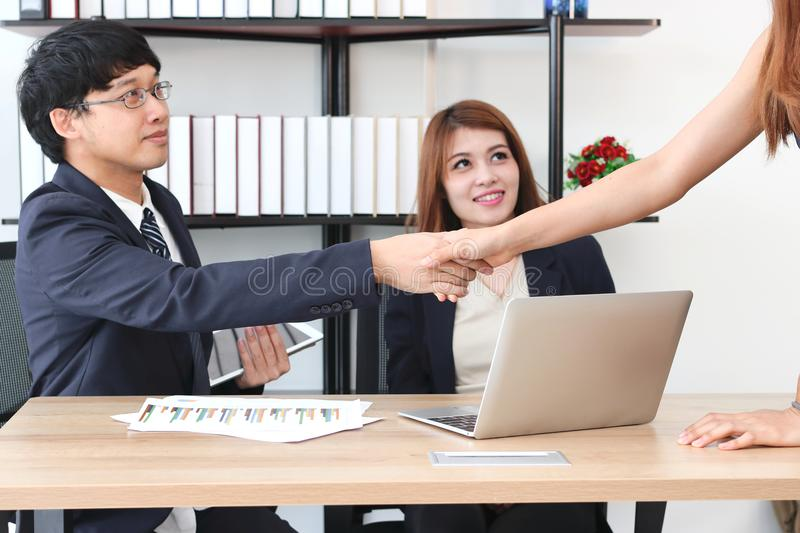 Young Asian business man shaking hands with partners after finishing a meeting. Handshake greeting deal concept. Young Asian business men shaking hands with stock images