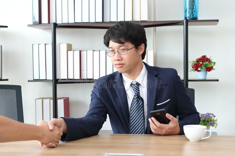 Young Asian business man shaking hands with partners after finishing a meeting. Handshake greeting deal concept.  stock image