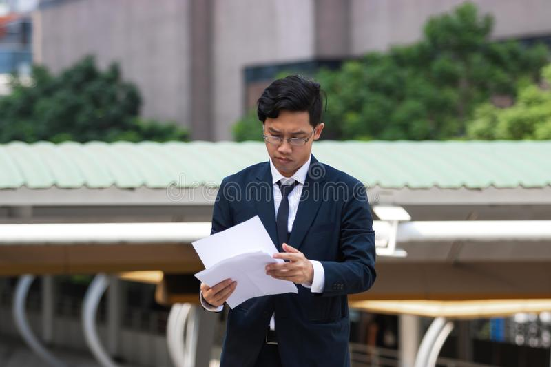 Young Asian business man in suit analyzing charts or paperwork in hands outdoors.  royalty free stock image