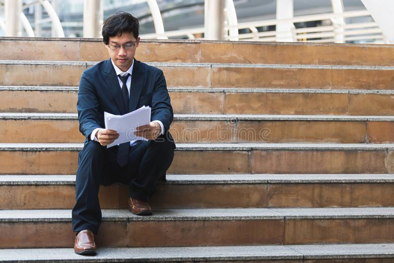 Young Asian business man in suit analyzing charts or paperwork in hands outdoors royalty free stock image