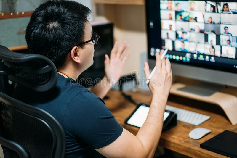 Young asian business man using computer for a online business meeting with his colleagues about plan in video conference. back. View of business man have webcam royalty free stock photos