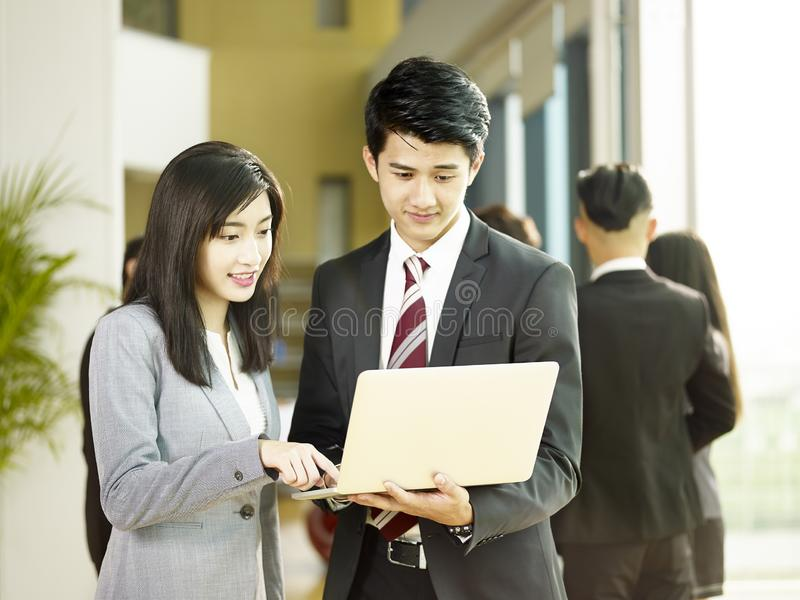 Young asian business man and woman working together in office stock photo