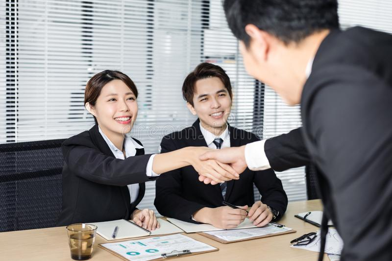 Young business people handshaking in conference room stock image
