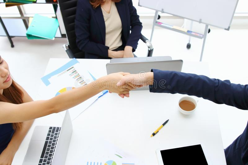 Young Asian business people shaking hands with partners after finishing a meeting. Handshake greeting deal concept royalty free stock images