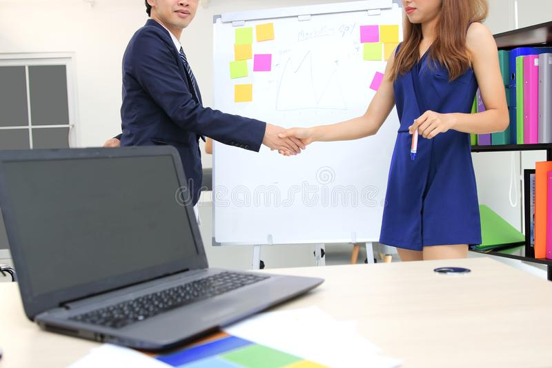 Young Asian business people shaking hands with partners after finishing a meeting. Handshake greeting deal concept stock photo