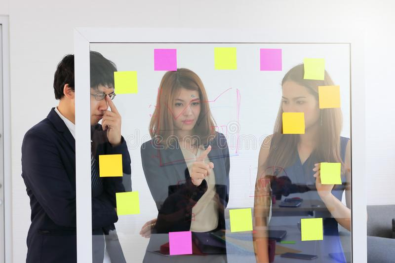 Young Asian business people use post it notes on glass wall to share idea at meeting room. Teamwork and brainstorm concept. stock photo