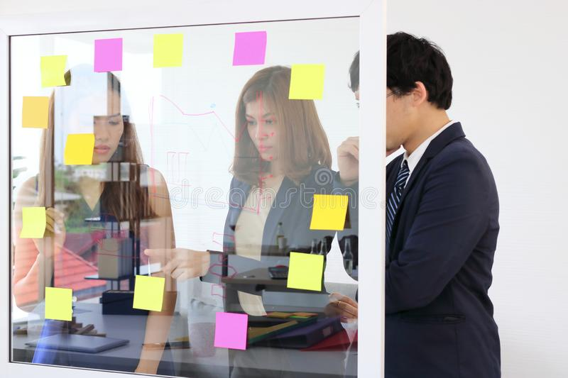 Young Asian business people use post it notes on glass wall to share idea at meeting room. Teamwork and brainstorm concept.  royalty free stock image
